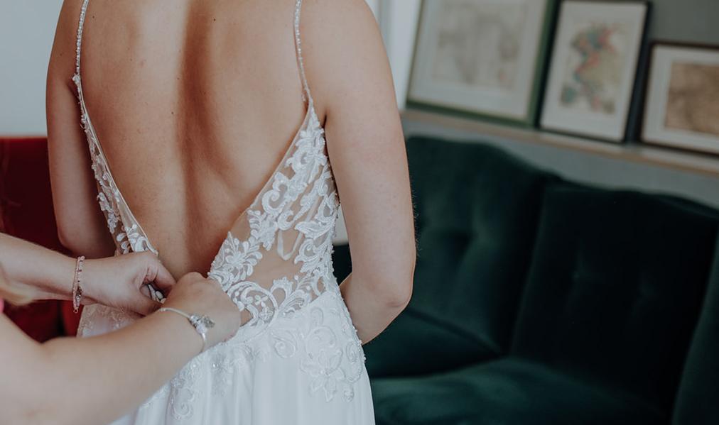 Zuknöpfen des Brautkleides