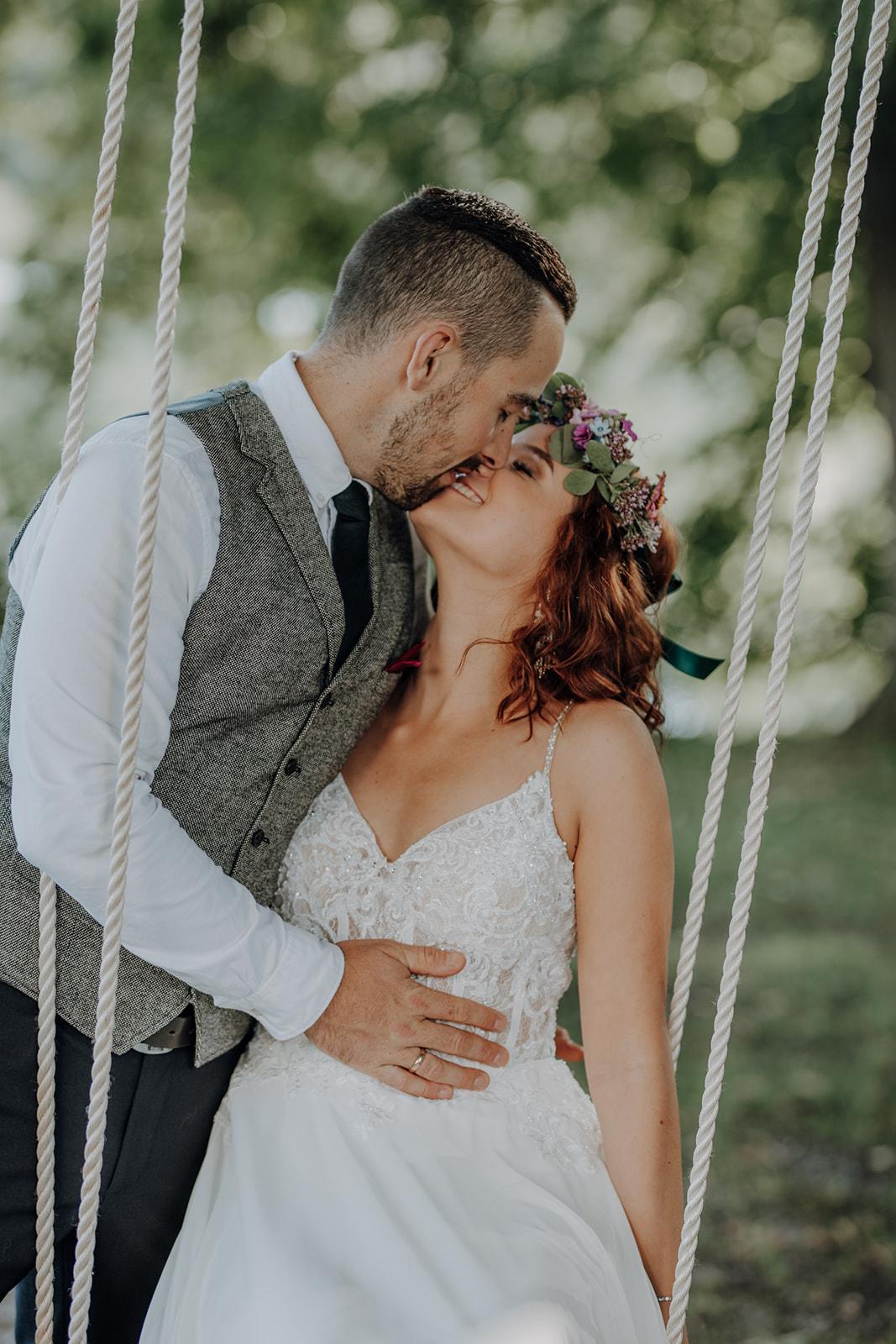 Brautpaar küsst sich auf Schaukel